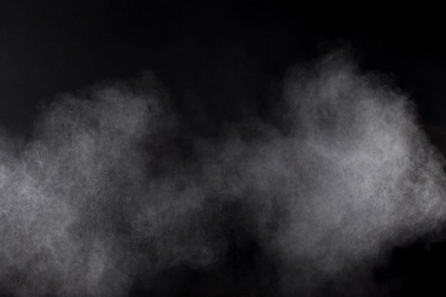 Forme bizzarre di nuvola di esplosione di polvere bianca su sfondo nero. spruzzata di particelle di polvere bianca. Foto Premium