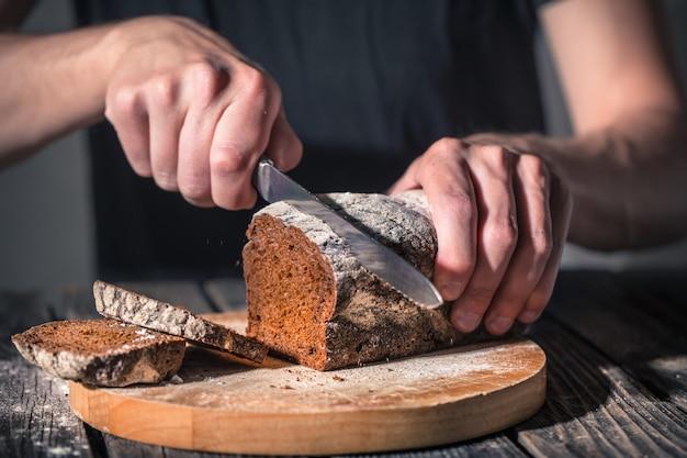 Fornaio che tiene il pane fresco nelle mani Foto Gratuite