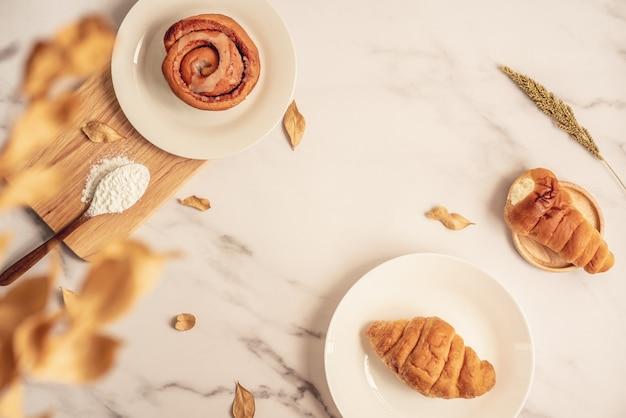 Forno fresco, panino alla cannella e cornetto fresco sul piatto con un cucchiaio di legno pieno di farina sul bordo di legno. dessert delizioso saporito sulla superficie di marmo bianca. colazione francese. vista dall'alto Foto Premium