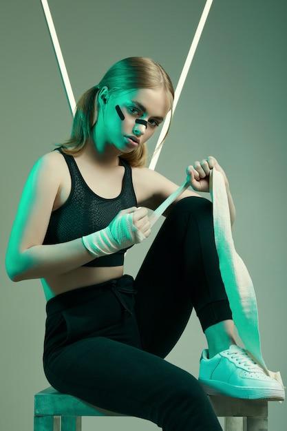 Forte bella donna con i capelli biondi, sguardo fiducioso, pugni in bende protettive per il pugilato Foto Premium