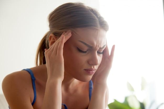 Forte concetto di mal di testa, giovane donna massaggiando..