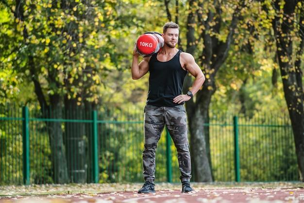 Forte lavoro maschile, fitness all'aperto. sollevamento di attrezzi pesanti. sportivo bello. giovane culturista. allenarsi in un campo sportivo. uomo sicuro. Foto Premium