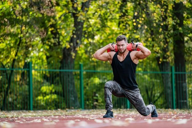 Forte lavoro maschile, fitness all'aperto. sollevamento di attrezzi pesanti. sportivo bello. giovane culturista. sta su un ginocchio e solleva un peso di 10 kg. Foto Premium