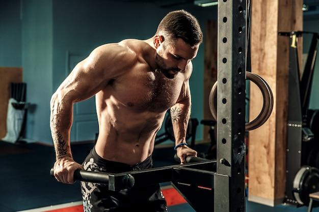 Forte uomo muscoloso facendo flessioni su barre irregolari nella palestra di crossfit Foto Premium