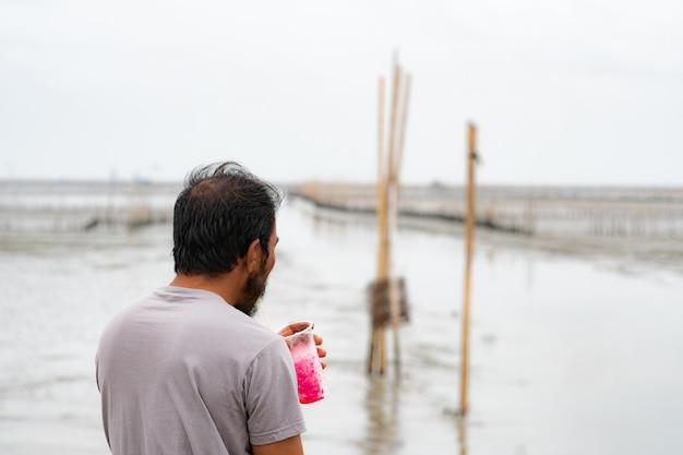 Foto da dietro, un uomo dai capelli corti con la barba, che beve bibite al mare Foto Premium