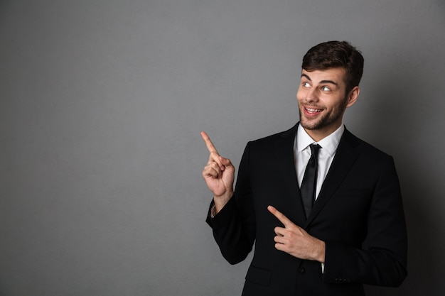 Foto del primo piano dell'uomo barbuto bello in vestito nero poiting con le due dita, guardante da parte Foto Gratuite