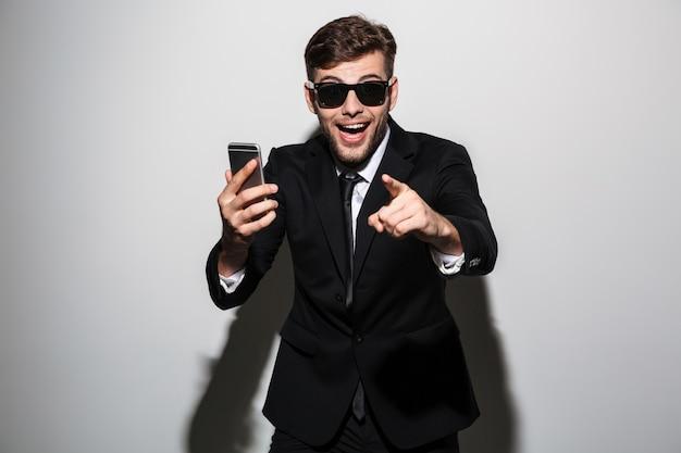 Foto del primo piano di giovane uomo attraente uscito felice in occhiali da sole che tengono smartphone e che indicano con il dito su voi Foto Gratuite