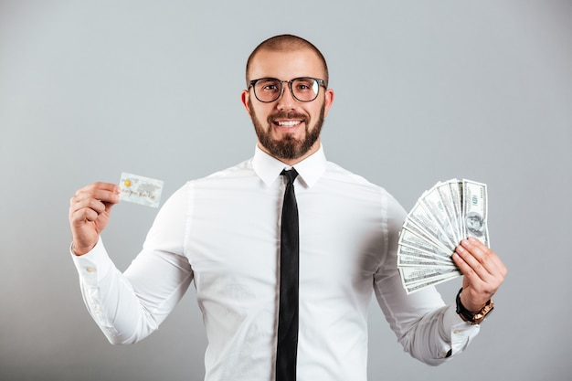 Foto dell'uomo ricco 30s in vetri e legame che mostra la carta di credito e fan delle banconote in dollari, isolato sopra la parete grigia Foto Premium