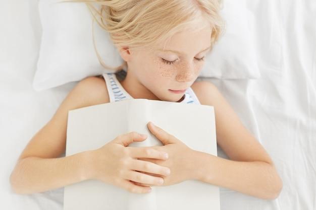Foto della bambina bionda con le lentiggini che sonnecchia nel letto, tenendo il libro in mano, sentendo stanchezza dopo una lunga lettura, addormentarsi. ragazza sonnolenta calma che si trova sui vestiti bianchi del letto con il libro. Foto Gratuite