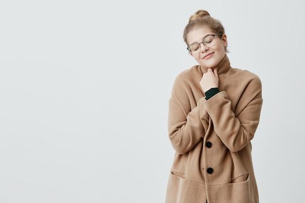 Foto della donna riposante con capelli biondi nel nodo che si avvolge in cappotto che ha sorriso sincero e soddisfatto, chiudendola nella posa di delizia. felice vita esultante femminile Foto Gratuite