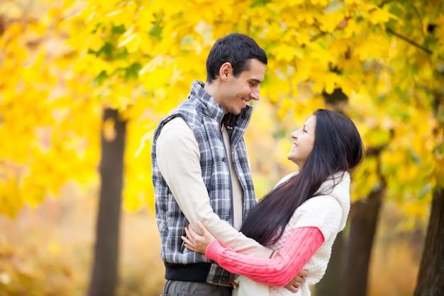 Foto delle coppie sveglie che abbracciano sui precedenti gialli meravigliosi degli alberi Foto Premium