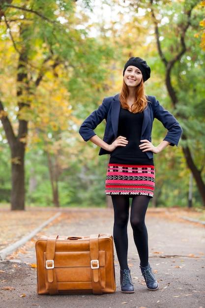Foto di bella giovane donna con la valigia sui precedenti meravigliosi del parco di autunno Foto Premium