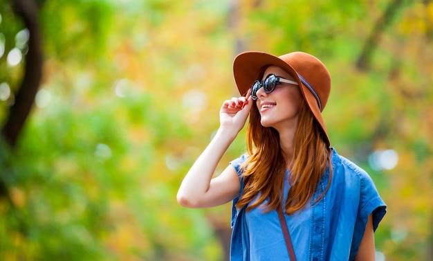 Foto di bella giovane donna in piedi sul meraviglioso parco in autunno Foto Premium