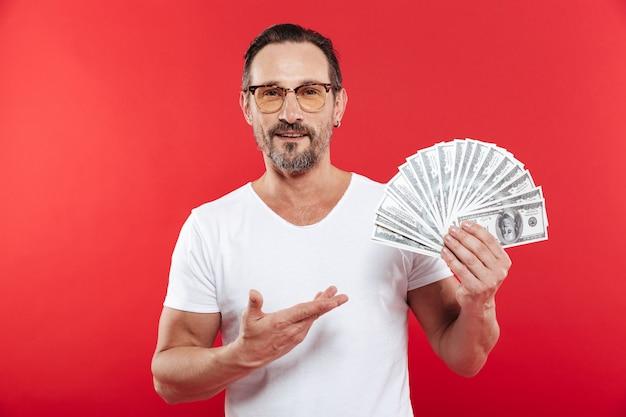 Foto di felice uomo vincitore in casual t-shirt bianca sorridente e dimostrando fan di soldi in banconote in dollari tenendo in mano, isolato sul muro rosso Foto Premium