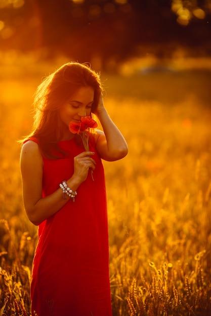 Foto di splendida signora in abito rosso in piedi in campo estivo d'oro Foto Gratuite