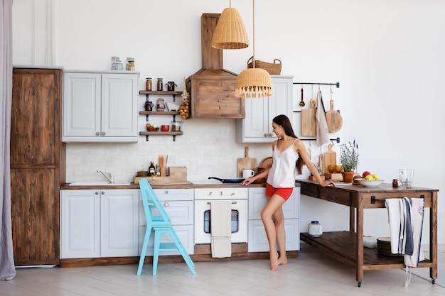 Foto di stile di vita della ragazza carina in piedi accanto alla stufa in cucina, cucinare e annusare aromi piacevoli dalla frittura di cibo Foto Premium
