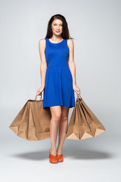 Foto di una giovane donna attraente che ostacola i sacchetti della spesa isolati Foto Gratuite