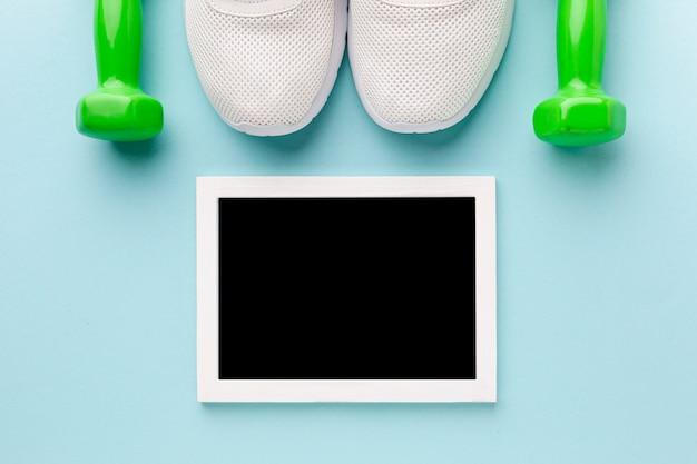 Foto di vista dall'alto mock up accanto a scarpe da ginnastica e pesi Foto Gratuite