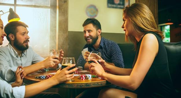 Foto di vista laterale degli amici maschii e femminili che si siedono alla tavola di legno. Foto Gratuite