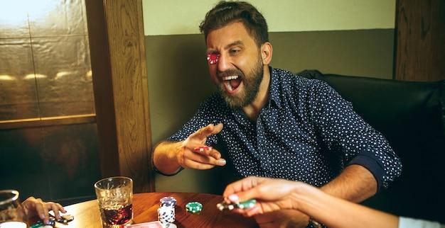 Foto divertente di amici seduti al tavolo di legno. amici che si divertono mentre giocano a gioco da tavolo. Foto Gratuite