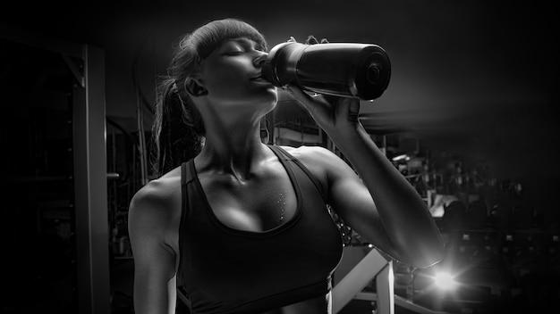 Foto in bianco e nero dell'acqua potabile della donna di forma fisica dalla bottiglia Foto Premium