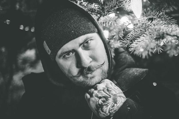 Foto in scala di grigi dell'uomo in berretto e felpa con cappuccio Foto Gratuite