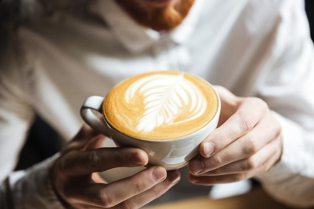 Foto potata dell'uomo in camicia bianca che tiene la tazza di caffè calda Foto Gratuite