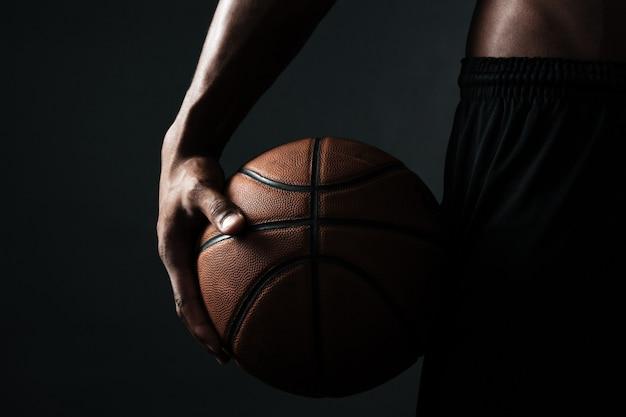 Foto potata della palla della tenuta del giocatore di pallacanestro Foto Gratuite