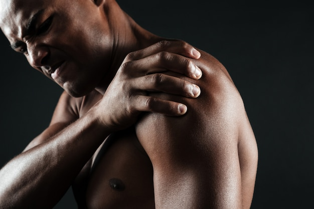 Foto potata di giovane uomo afroamericano senza camicia con dolore alla spalla Foto Gratuite