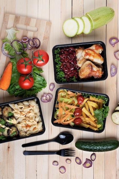 Foto verticale di contenitori in plastica nera per alimenti. vista dall'alto sul tavolo di legno, pasto pronto Foto Premium