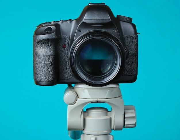 Fotocamera digitale moderna con un treppiede sul tavolo blu. vista frontale Foto Premium