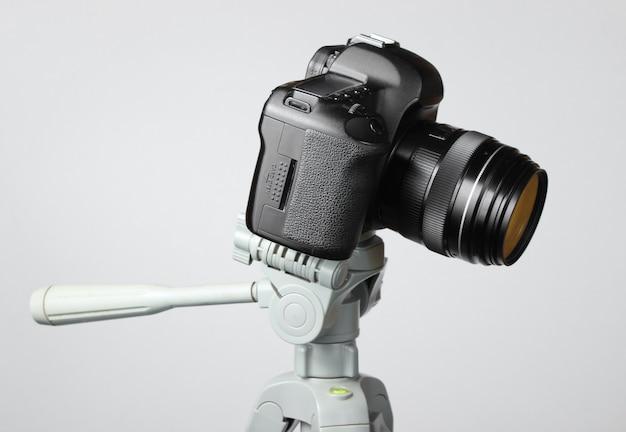 Fotocamera digitale moderna con un treppiede sul tavolo grigio Foto Premium