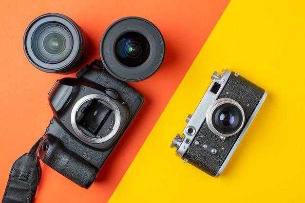 Fotocamera reflex digitale e pellicola con una serie di obiettivi su un tavolo colorato, i progressi delle attrezzature fotografiche Foto Premium