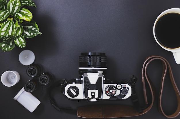 Fotocamere d'epoca e rotoli di pellicola, caffè nero, alberi collocati su uno sfondo nero Foto Premium