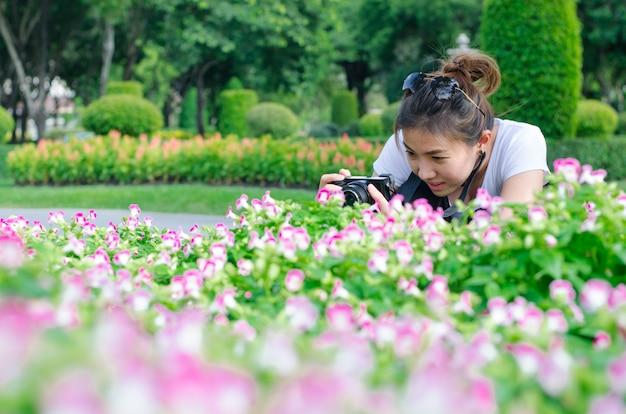 Fotografia femminile con fotocamera scattare una foto di fiori Foto Premium