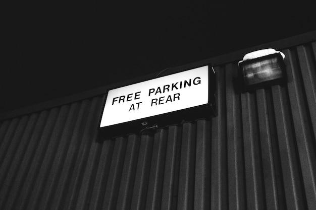 Fotografia in scala di grigi del parcheggio gratuito al cartello posteriore Foto Gratuite