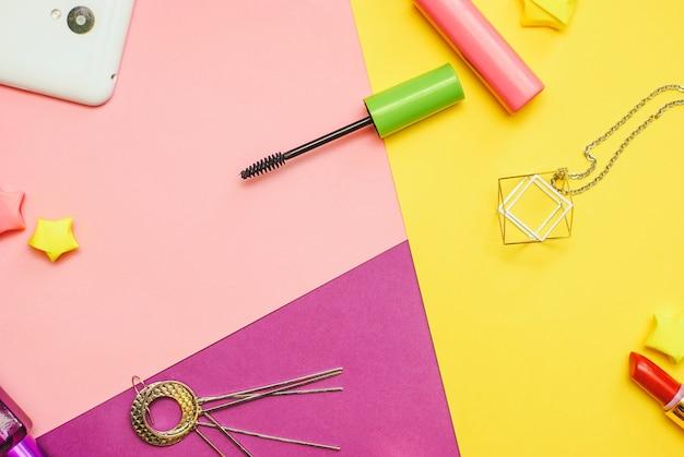 Fotografia piatta laica con cosmetici e accessori su sfondo colorato Foto Premium