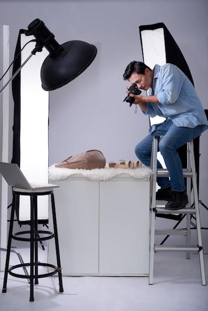 Fotografo asiatico che si siede sulla scala in studio con la macchina fotografica e che prende le foto degli oggetti di modo Foto Gratuite
