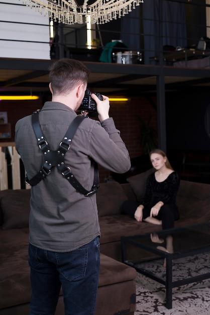 Fotografo che cattura le immagini del modello sul divano Foto Gratuite