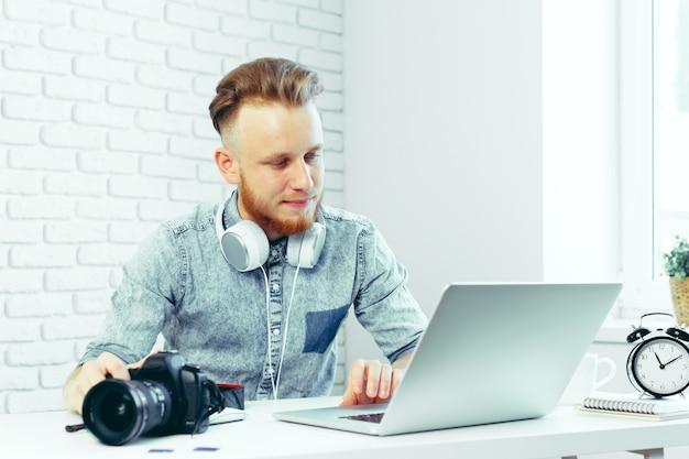 Fotografo che seleziona le foto sul suo computer Foto Premium