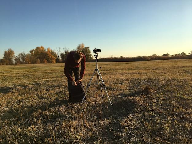 Fotografo che utilizza il treppiede e realizza la fotografia paesaggistica Foto Premium