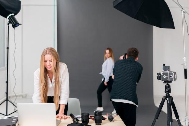 Fotografo con il modello e la donna che lavora al computer portatile dalla vista Foto Gratuite