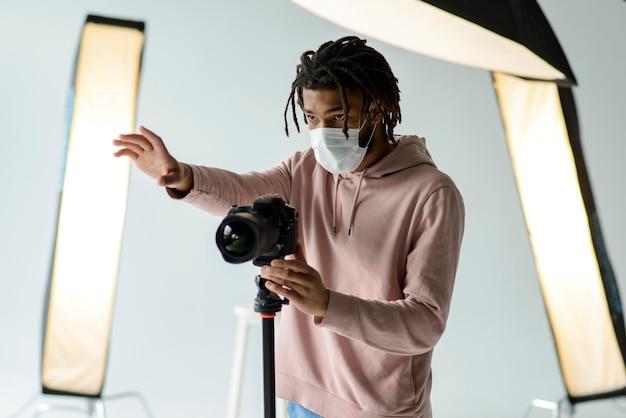 Fotografo con maschera medica Foto Gratuite