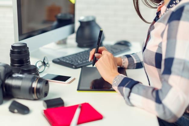 Fotografo grazioso della giovane donna con la macchina fotografica in ufficio Foto Premium