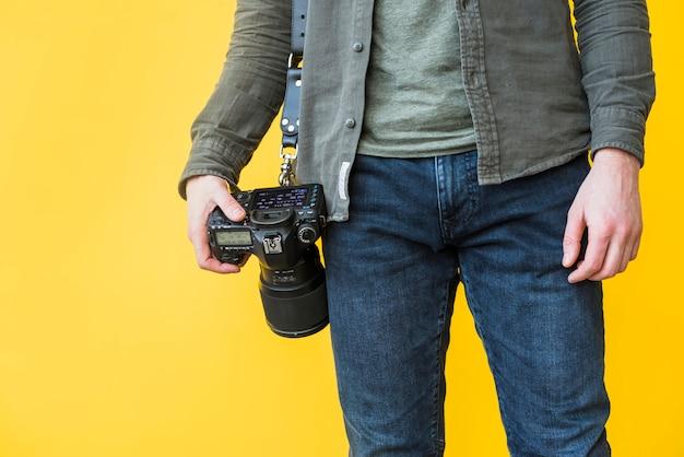Fotografo in piedi con la macchina fotografica Foto Gratuite