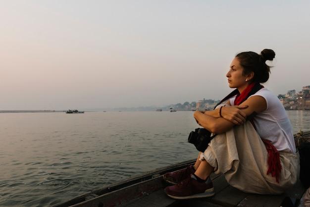 Fotografo seduto su una barca sul fiume gange Foto Gratuite