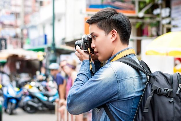 Fotografo turistico maschio asiatico che prende foto alla strada di khao san nella città di bangkok Foto Premium