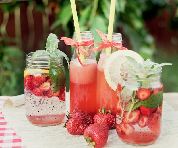 Fragola e menta hanno infuso acqua detox. limonata alla fragola con ghiaccio e menta come bevanda rinfrescante estiva in barattoli. bevande analcoliche fredde con frutta. Foto Premium