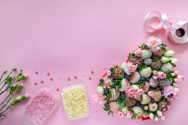 Fragole, fiori e decorazione coperti di cioccolato fatti a mano per la cottura del dessert su fondo rosa con spazio libero per testo Foto Premium
