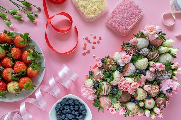 Fragole, fiori e decorazione coperti di cioccolato fatti a mano per la cottura del dessert su fondo rosa Foto Premium